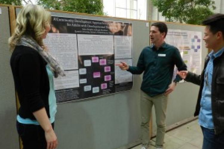 Adam Broad (C) and Ashleigh Blinkhorn (L) share their poster with fellow OT student Pablo Chang (R).
